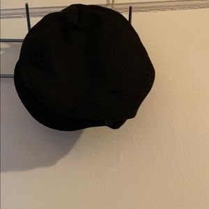 Never worn hat with two black buttons on the brim.